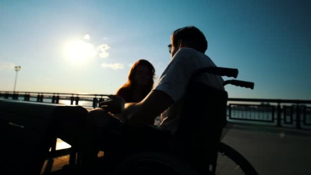 Young Man Sitting In A Wheelchair And Talking To A Girl Outdoor