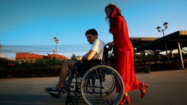 schöne rothaarige Mädchen rollt Kerl im Rollstuhl auf der Promenade am Abend, Nahaufnahme