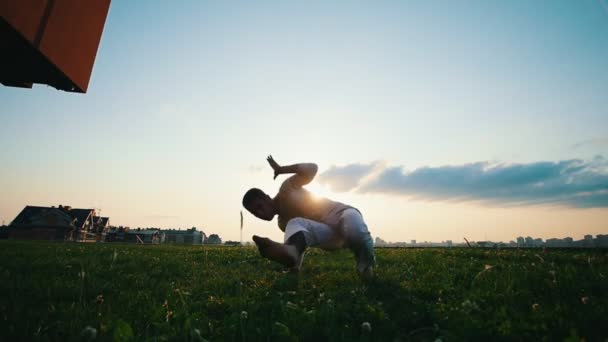 Athletic male trains capoeira on grass against the sun on summer evening