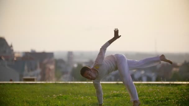 Athletic male showing the technique of the dance of capoeira on the background of the city