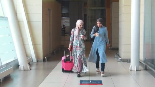 Two Muslim girls walk, talk and drink coffee