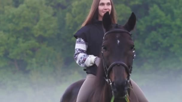 Beautiful girl with long hair rides a horse, a horse chews grass, fog around, early morning