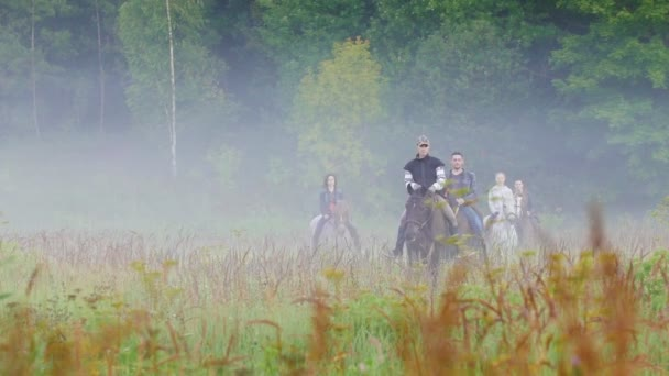 The company of young people walking on horseback in nature, all around the fog