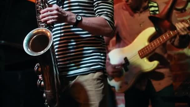 Saxophonist and guitarist masterly play at a performance in a jazz bar