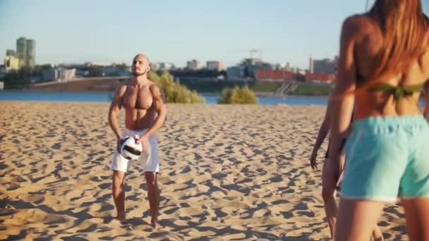 Sport muž s nahý trup je míč, zatímco hraje plážový volejbal