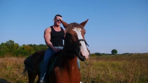 Strong man bodybuilder in a black t-shirt, denim pants, sunglasses riding a horse