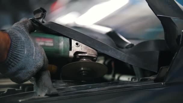 Mechaniky ruce brousí část vozu s bruskou
