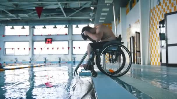 Disabled man in a wheelchair putting on a swimming cap and a goggles ...