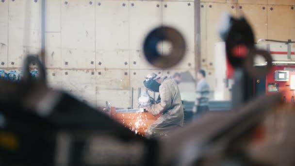 Svářeč v průmyslové továrně pracuje v speciální oblek a maska