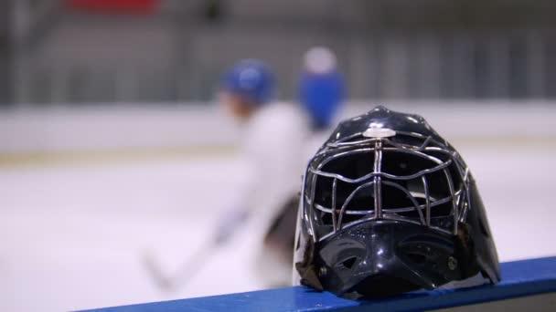 Hokejové helmy uzavřít proti pozadí hokejisté hrají na hřišti hokej