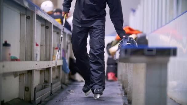 Hokejista v bruslích jde na místě pro náhradní hráči u zimního stadionu. Pohled zepředu
