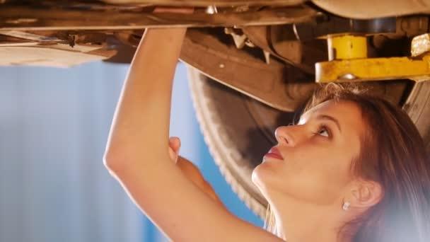 sexy Mechanikerin repariert das Auto mit einem Schraubenschlüssel. Seitenwinkel. Blick nach oben. Nahaufnahme