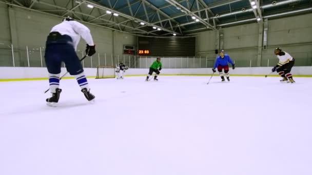Tým hraje hokej na ledě během tréninku. Zpomalený pohyb.