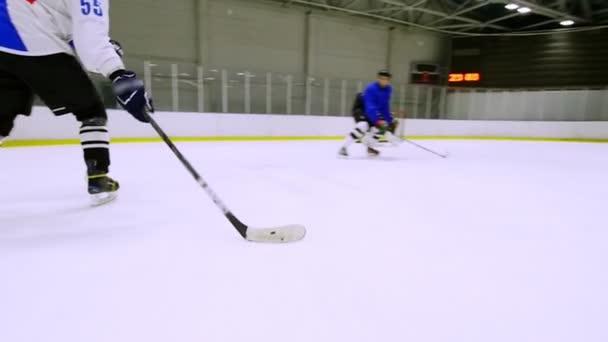 Hokejista dává průchod na spoluhráče během hokejového zápasu