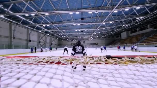 Hokejový brankář stojí u brány během hokejový zápas na ledě. Zpomalený pohyb