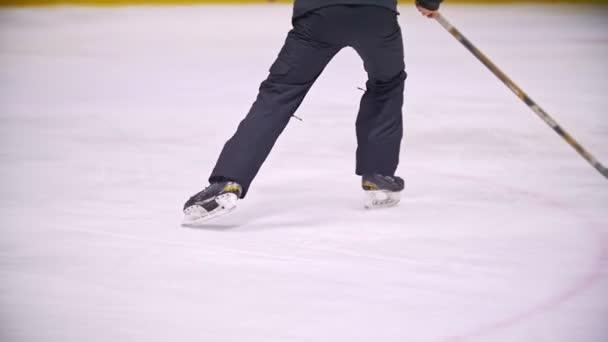 Hokejista vede PUK a běží na ledě během hokejového zápasu. Pohled z zadní