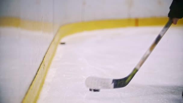Hokejový brankář hodí puk do ohradní zeď