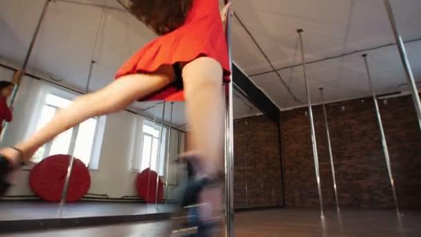 Sexy dívka v červených šatech s létající vlasy pól tanec