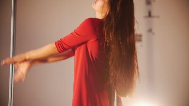 Sexy dívka v červených šatech Poláka tanec. Točí kolem pólu. Nohy vám