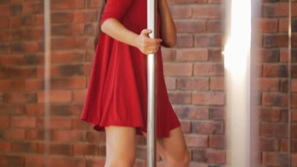 Sexy dívka v červených šatech se připravuje na školení její pól tanec