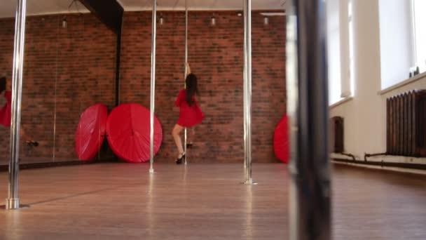 Sexy dívka v červené šaty, sestupuje z pólu a pokračuje směrem k fotoaparátu