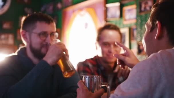 Three guys drinking beer in a pub and discuss something.