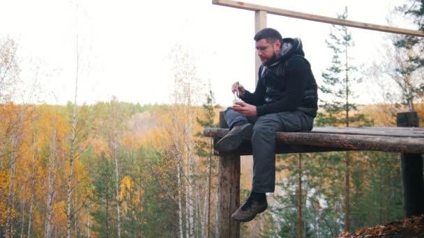 ein Mann sitzt in großer Höhe und isst die Konserven mit einem Messer