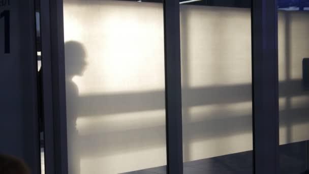 Männer und Frauen Silhouette zu Fuß durch Flur.