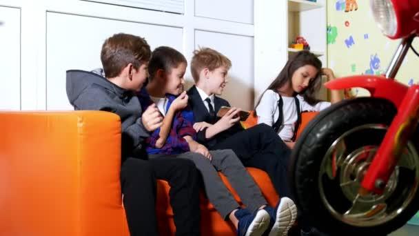 Tři kluci a jedna dívka sedí na pohovce a hraní videoher na mobilním telefonu