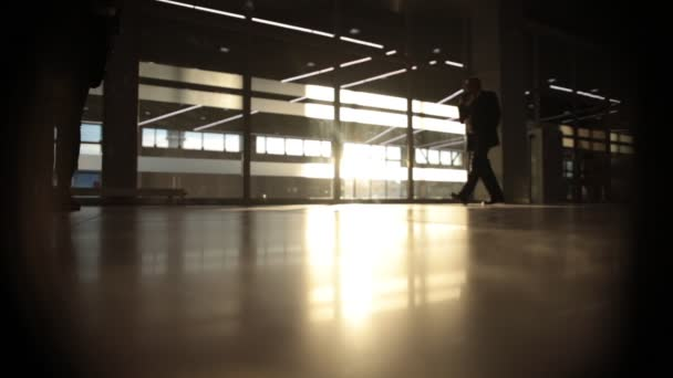 backlight silhouette of man walking in front of big window