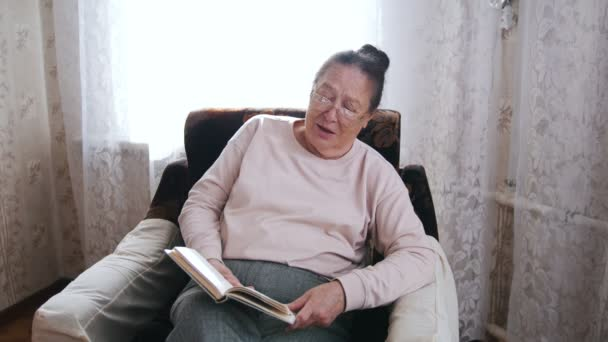An elderly woman sitting in a armchair and reading aloud on the background of the window.