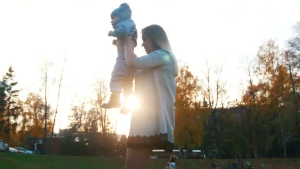 Young mother lifts up on hands her little baby son and puts him on her shoulders. Happy family