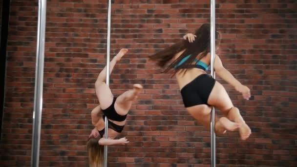 Dvě dívky cvičí pozice ve třídě fitness pól na pozadí cihlové zdi. Dynamický pylonu. Zpomalený pohyb