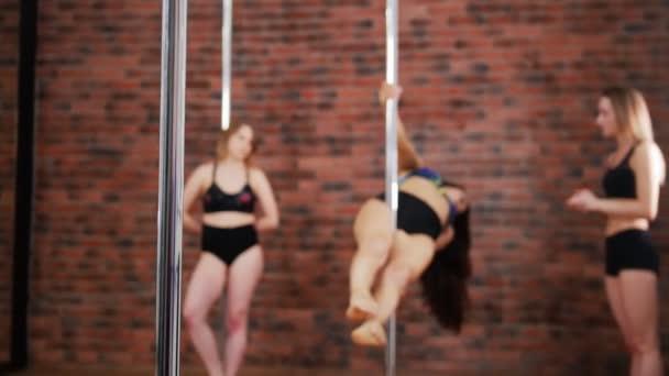 Dvě sportovní dívky zlepšuje dovednosti v třídě fitness pól s instruktorem. Dynamické pylon