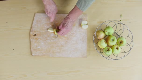 An old woman cutting apple on pieces