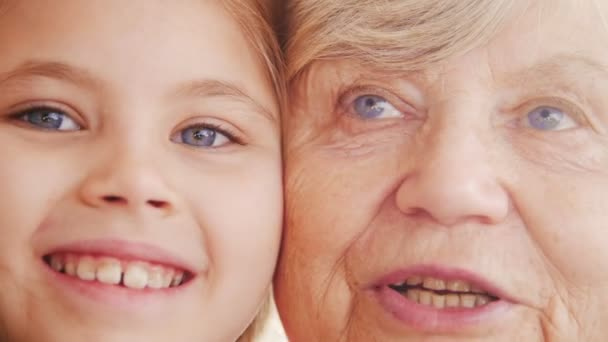 Close up portrait of grandmother and granddaughter. Bright violet eyes