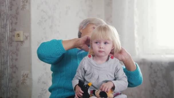 Grandmother brushing her granddaughters blonde hair
