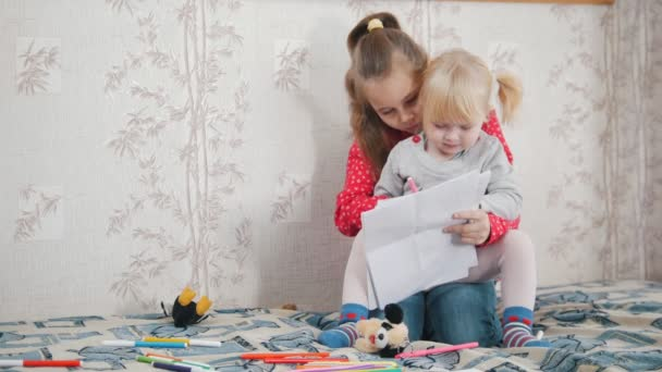 Two little girls sitting on the bed and writting something
