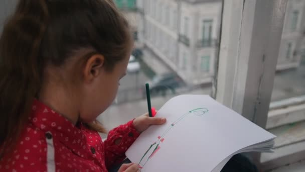 A girl sitting on the windowsill and drawing something