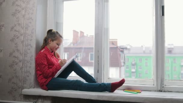A smiling girl in red shirt sitting on the windowsill and drawing with colour pencils