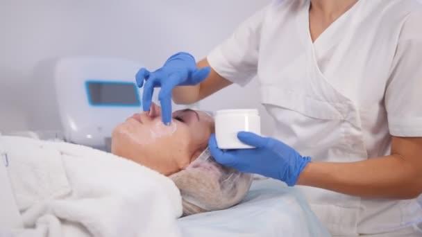 Kosmetologické procedury. Léčba loupání. Rozmazání krém na obličej