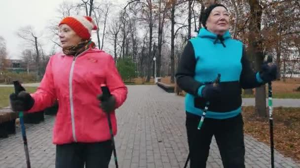 zwei alte Frauen auf Nordic-Walking-Stöcken auf dem Bürgersteig