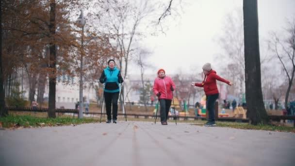 Eine ältere Frau gibt Handzeichen und zwei ältere Frauen beginnen mit Nordic-Walking-Stöcken zu gehen. Zeitlupe