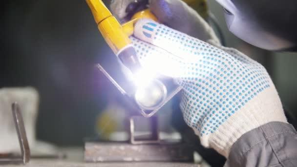 Průmyslové výroby. Pracovník v rukavicích na svařování. Detailní práce