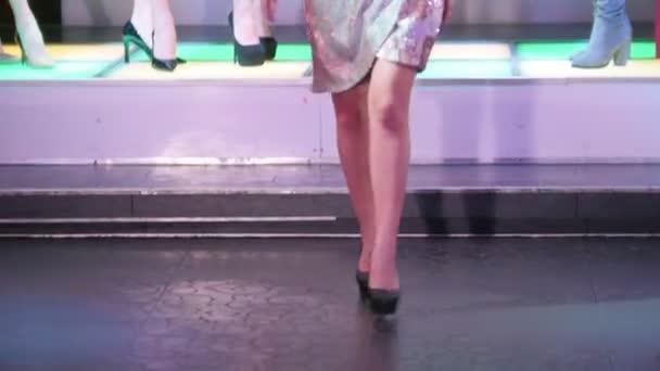 Módní přehlídka. Ženské modely chůze na dráze v šatech na paty
