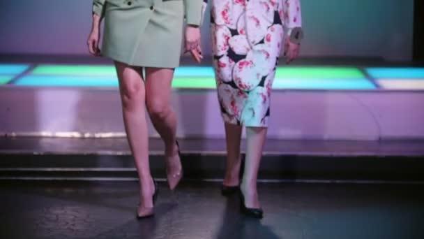 Módní přehlídka. Ženské modely chůze na dráze v šatech na paty. Zpomalený pohyb