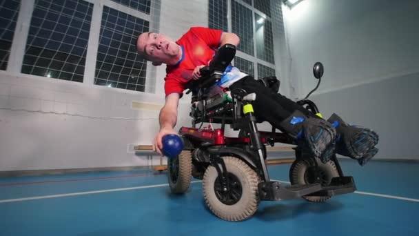 Postižený člověk v invalidním vozíku. Házení modrý míček