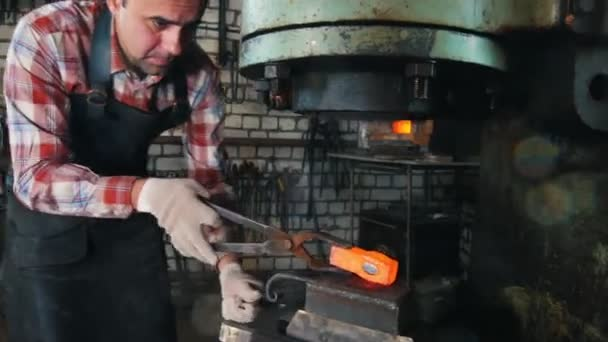 Blacksmith at work with electric hammer near the anvil, red hot steel, forge