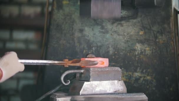 Blacksmith working with electric hammer on the anvil, man making right  shape of red hot steel, craft