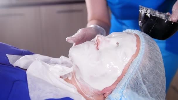 Beauty clinic. Mladá žena dostane zacházení kosmetologie. Rozmazání bílé anti-aging tekutý masky na obličej.